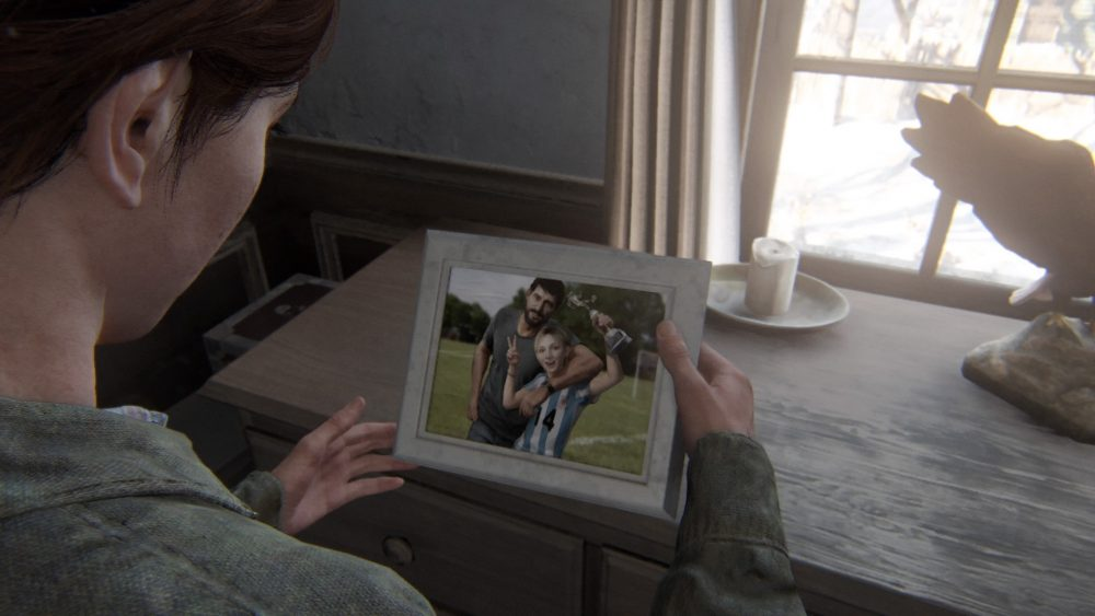 Ellie holds a photograph of Joel and his late daughter Sarah that she found in Joel's home. Sarah is in a soccer jersey, flashing peace signs at the camera, and Joel has his arm slung around her shoulders.