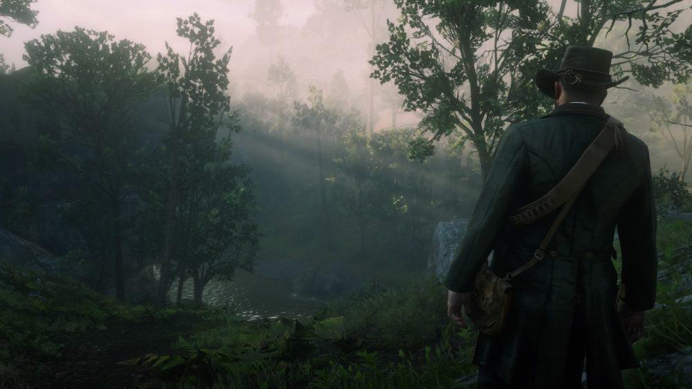 A screenshot of Arthur Morgan standing and looking over the creek below Beaver Hollow. Red Dead Redemption 2, Rockstar North, Rockstar Games, 2018.