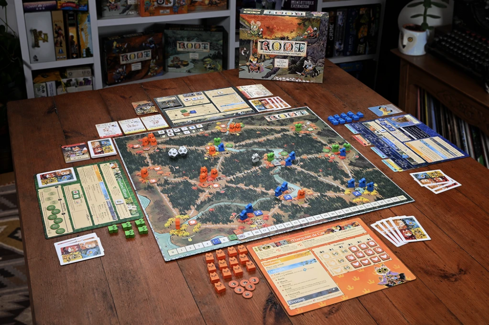 A typical tabletop setup of the board game version of Root. There's a map in the center, and each player has an info sheet for their faction, several cards, and a number of tokens. There are also two twelve-sided dice on the board. Root, Leder Games, 2018.