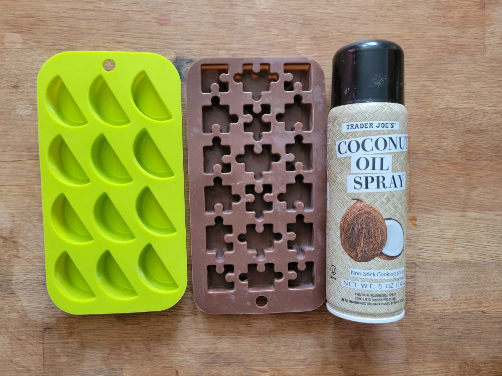 Two silicone candy molds and a can of coconut oil spray.