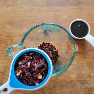 A photo of loose hibiscus and rose hips tea leaves, and date syrup.