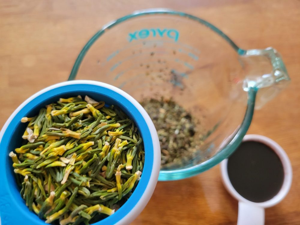 A photo of loose lotus and mint tea leaves, and date syrup.