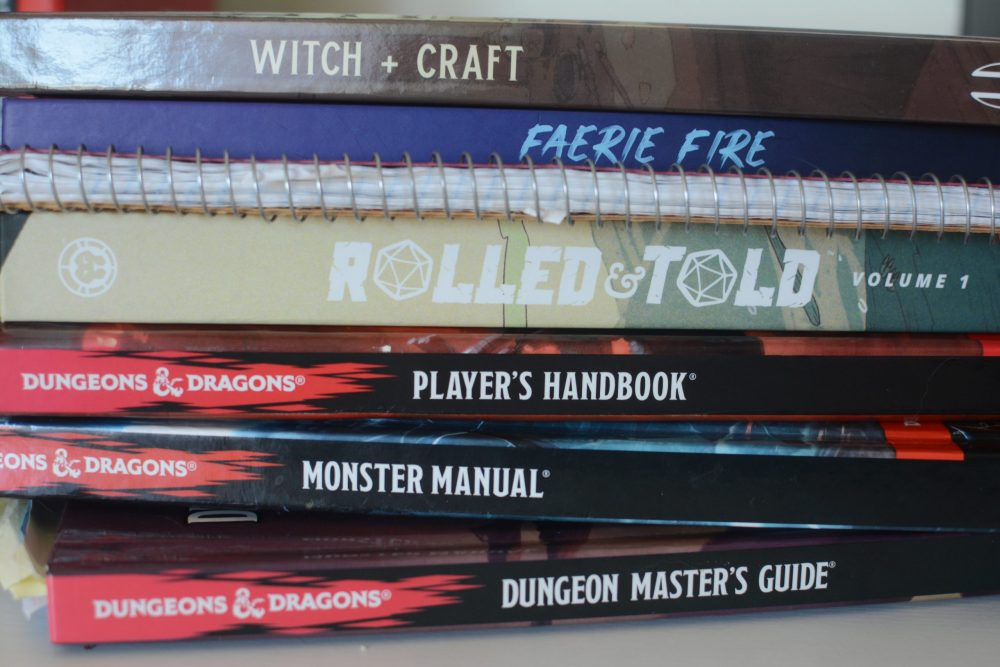 A photo of a stack of books. From top to bottom: Witch+Craft, Faerie Fire, a notebook, Rolled and Told Volume 1, the D&D Player's Handbook, Monster Manual, and Dungeon Master's Guide.