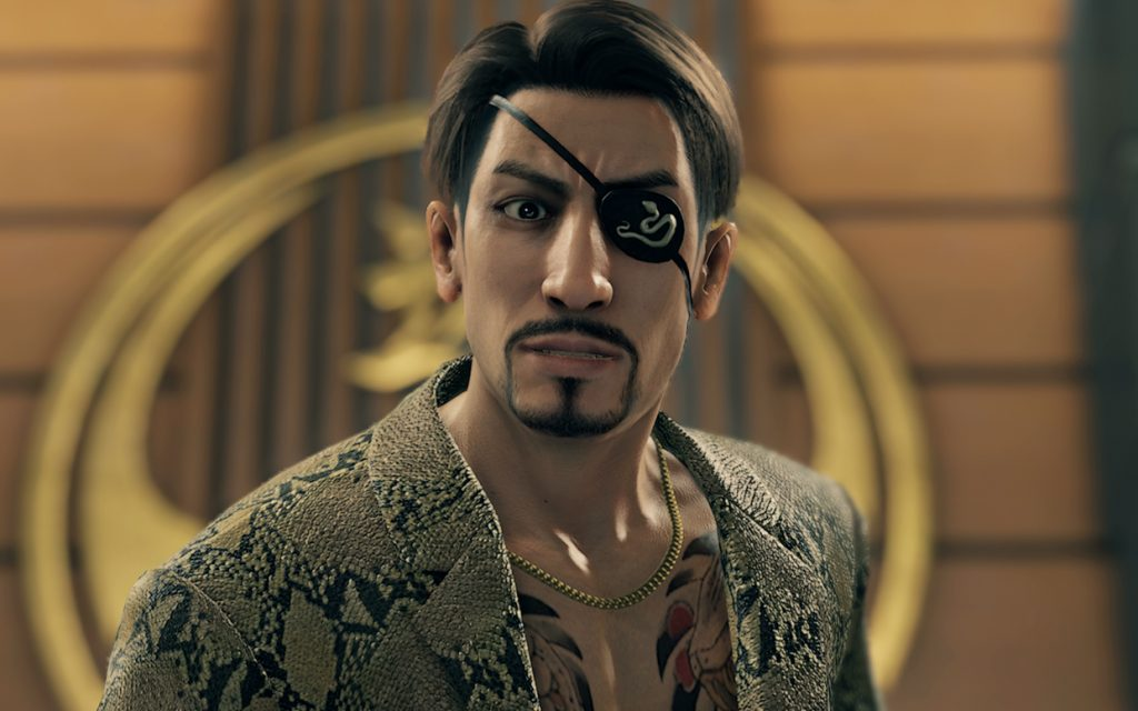 Goro Majima, a man with a thin face, a goatee, and an eyepatch with a snake design on it, stares into the camera. He is wearing a snakeskin blazer over two chest tattoos, a heavy gold chain, and no shirt.