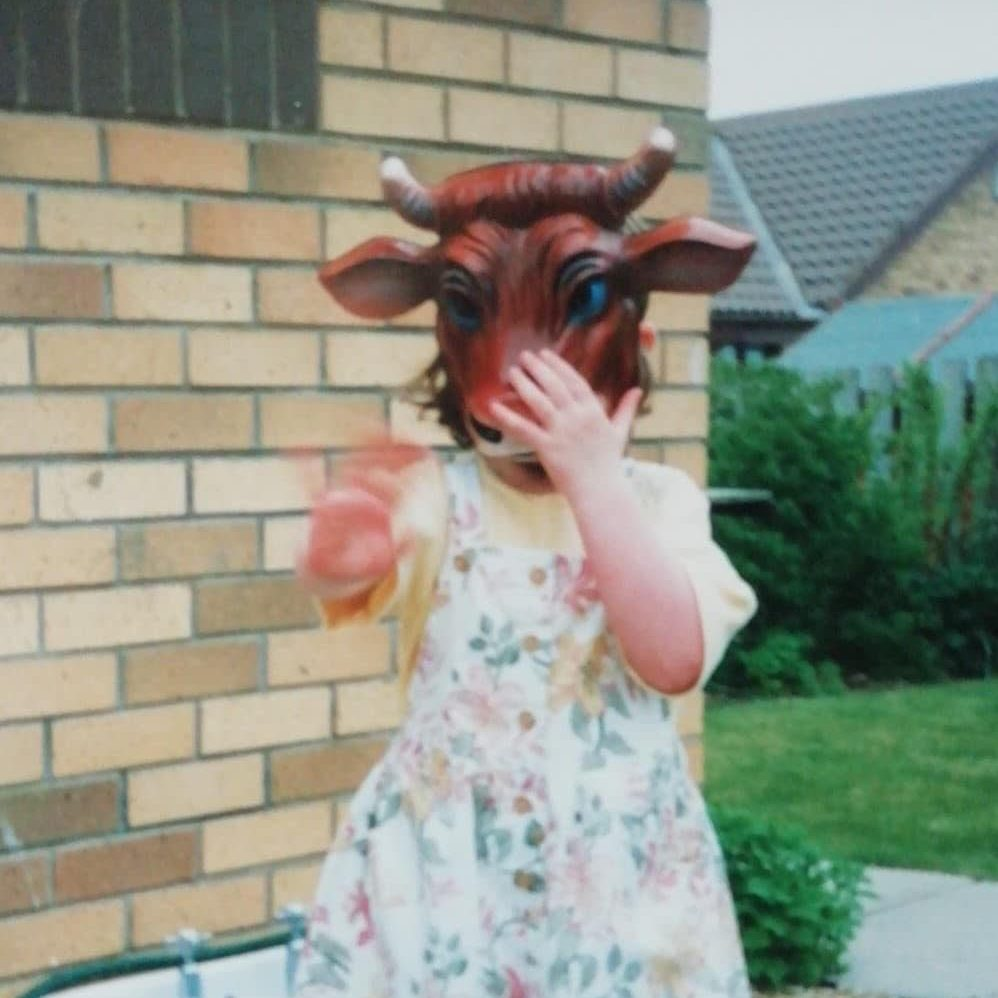 A photo of a young girl in a dress holding a cow mask over her face.