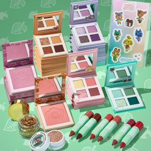 An assortment of various makeup color palettes and pencils set on a green, leaf patterned backdrop.