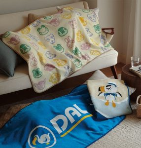 """A tight snapshot of a living room. An off-white towel with a pattern of cartoon animal faces covers a portion of couch. Two other towels lie on the floor: a long, blue towel that reads """"DAL"""" is underneath a folded towel with the design of a pelican in a sailor outfit laying asleep on a shoreline."""