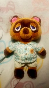 A stuffed, bear like plushie with a stoic expression, wearing a collared, short sleeved button up shirt, lays flat on a blanket.