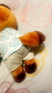 A closer detail of a stubby tail attached to the behind of a stuffed, bear like plushie.