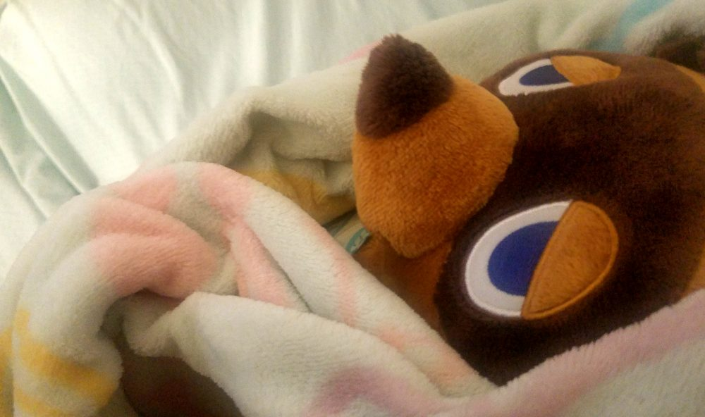 A stuffed, bear-like Tom Nook plushie with a stoic expression is swaddled in blankets.