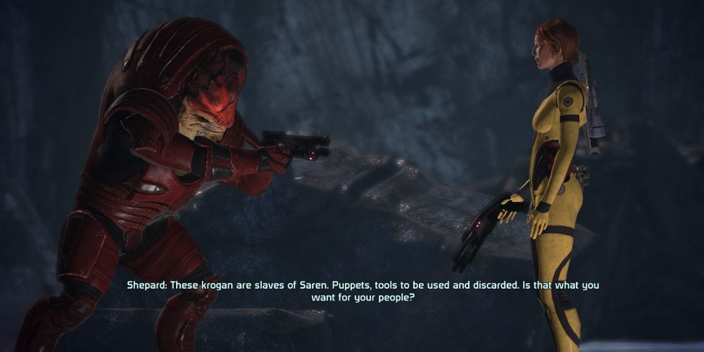 """A screenshot from Mass Effect 1. Squad member Wrex points a gun at Shepard, who says, """"These krogan are slaves of Saren. Puppets, tools to be used and discarded. Is that what you want for your people?"""" Image source: https://www.thegamer.com/mass-effect-how-to-keep-wrex-alive-on-virmire/. Mass Effect Legendary Edition, BioWare, Electronic Arts, 2021"""